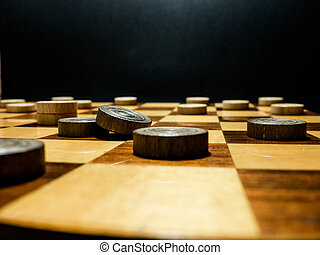 wooden draught pieces on a wooden draughtboard in a dark background