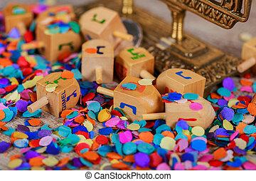 Wooden dreidel for Hanukkah on light background