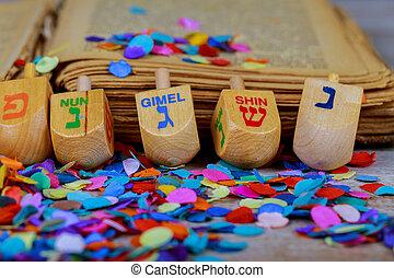 wooden dreidels spinning top for hanukkah jewish holiday over glitter background