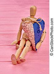 Wooden dummy holding big heart.
