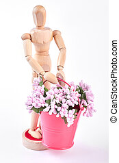 Wooden dummy holding bucket with flowers.