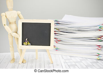 Wooden dummy holding empty blackboard with woman is cycling