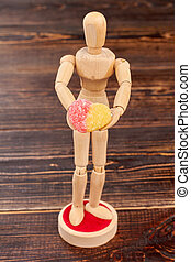 Wooden dummy holding heart-shaped candy.