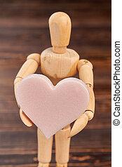 Wooden dummy holding pink soft heart.