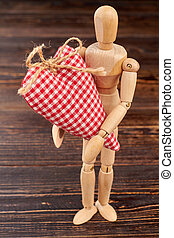 Wooden dummy holding red checkered heart.
