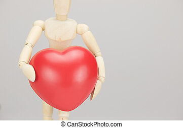 Wooden dummy holding red heart with white background