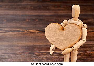 Wooden dummy holding wooden heart.