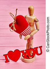 Wooden dummy mannequin in love holding heart.