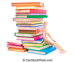 Wooden dummy puppet sitting on books