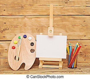 Wooden easel with clean paper and wooden artists palette...