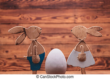 wooden easter bunnies facing each other near big egg