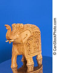Wooden elephant sculpture on blue background