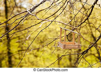 feeding trough for birds on a tree