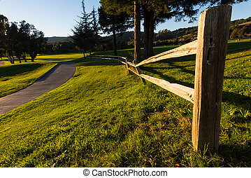 Wooden fence along a walking path with grass