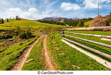 wooden fence along the dirt road on grassy hills of...