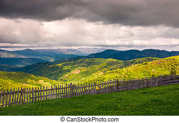wooden fence along the grassy hillside. beautiful springtime...