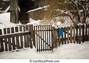 Wooden fence and gate near the house. Snowy winter on the street in the Russian village.