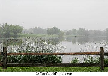 Wooden Fence Framing Lake on Rainy Day