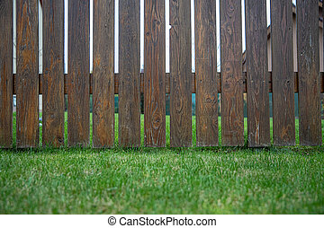 wooden fence in front of green garden of family house