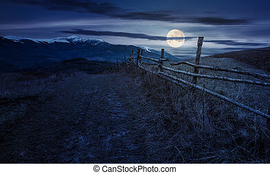 wooden fence in mountainous countryside at night in full...