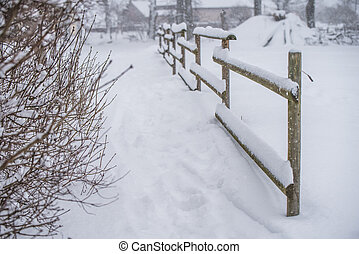 Wooden fence in the snow on winter country background