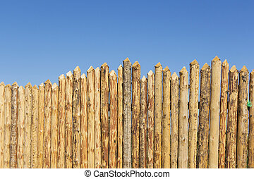 Wooden fence made of sharpened planed logs. - Wooden fence...
