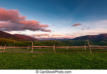 wooden fence on a grassy hill at sunset. beautiful rural...