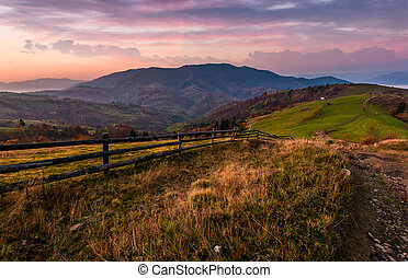 wooden fence on a grassy hillside at autumn dawn - wooden...