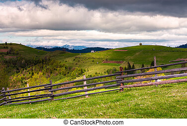 wooden fence on a grassy slope of Carpathian alps. beautiful...