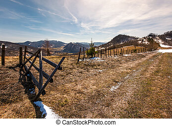 wooden fence on a hillside in springtime. beautiful...
