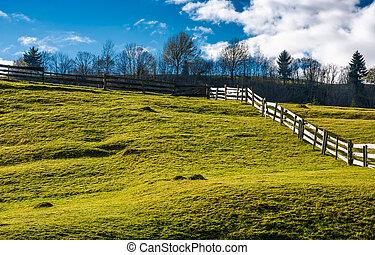 wooden fence on grassy hillside in autumn. wonderful rural...