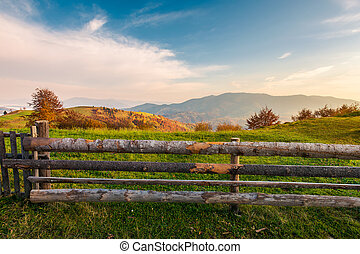 wooden fence on grassy rural field. distant mountain in...