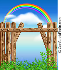 Wooden fence on green grass and rainbow
