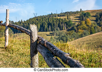 wooden fence on hillside near forest - wooden fence wrapped...