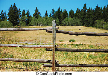 Wooden fence on ranchland - Wooden fence with ranchland and ...