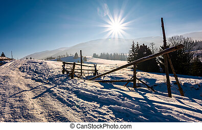 wooden fence on snowy meadow. lovely rural scenery on a...