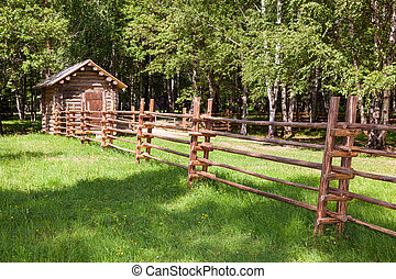 Wooden fence with small wooden house in countryside