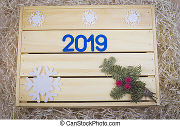 Wooden festive background. Blue symbol with number 2019 and new year decor on wooden background