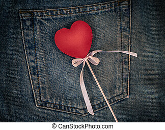 Wooden figure of heart on the background of the back pocket of blue jeans, full frame