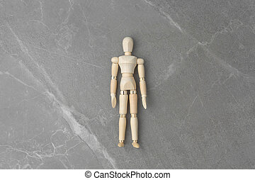 Wooden figure on isolated gray marble background.