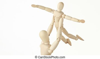 wooden figures of parent carrying his child over head, child aparting hands