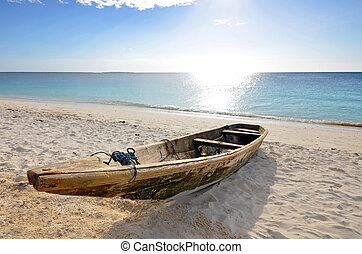 Wooden Fishing boat on a beach with blue sky