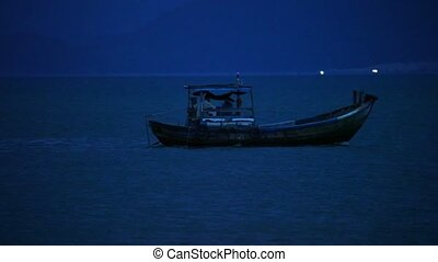 Fisherman in a small wooden fishing boat navigating across the south china sea, night fishing high definition stock footage clip.