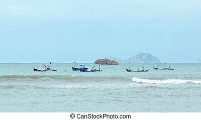 Several handmade, wooden fishing boats bob at anchor in the shallow waters off a tropical beach near Nha Trang, Vietnam.