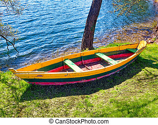 Wooden Fishing boats on shore of Galve lake Trakai Lithuania in spring. Old wooden boat in grass on the lake bank