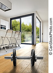 Modern apartment interior with dumbbells in foreground