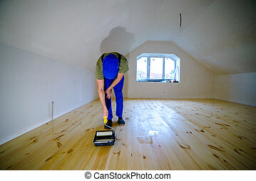 varnished - Wooden floor varnished. Worker with paint...