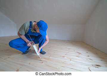 varnished - Wooden floor varnished. Worker with silicon gun.