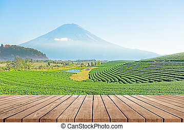 Wooden floor with beautiful landscape of tea plantation background.