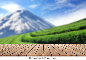 Wooden floor with blurred beautiful landscape of tea plantation background.